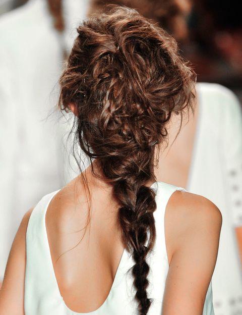"""<p> Según Corral Calero, """"el pelo necesita estar en estupendo estado para sostener un peinado casual como éste. Aunque existe algo de brillo, las largos de pelo tienen un aspecto semi-mate (logrado gracias al nuevo Estimulador de Raíces Moroccanoil y a la nueva Crema Moldeadora Moroccanoil - ambos lanzados esta temporada en el Fashion Week). El cabello puede seguir teniendo movimiento en cualquier dirección y verse y sentirse bien gracias a la aplicación en seco del Tratamiento Moroccanoil"""".<br /> 1. """"Comencé con una base de Tratamiento Moroccanoil sobre el pelo seco para acondicionar, fortalecer y suavizar, luego rocié con el nuevo Estimulador de Raíces Moroccanoil (disponible a partir de 2014) en las raíces comenzando por la nuca y siguiendo hacia arriba. Además, apliqué el Tratamiento Moroccanoil sobre el pelo seco para aportar una mejor tracción y agarre en la aplicación de los productos que utilicé a continuación"""". <br /> 2. """"Luego le siguió la nueva Crema Moldeadora Moroccanoil. Apliqué un poco del producto entre mis dedos y lo apliqué desde las raíces hasta las puntas. Éste fue un producto clave para la obtención del look, debido a que le dio la textura adecuada semi-mate con el suficiente brillo. Era importante que el cabello luciera saludable y no demasiado seco"""".<br /> 3. """"El paso siguiente fue secar el cabello desde abajo y levantarlo desde la raíz con mis dedos, dejándolo al viento. Era muy importante no tirar o tratar de controlar el cabello"""". <br /> 4. """"Una vez que el cabello estuvo totalmente seco, y con las cabezas de las modelos inclinadas hacia abajo, masajeé el cabello en las raíces y lo elevé para intensificar su textura enredada.""""<br /> 5. """"Distribuí el pelo de oreja a oreja y lo fijé, mientras hacía una trenza con los mechones restantes en la nuca"""". <br /> 6. """"Solté el pelo de arriba y luego metí diferentes partes de los mechones en la trenza, como el estilo macramé, y lo mezclé con las ondas, creando un cabello suelto con forma de pirámide inv"""