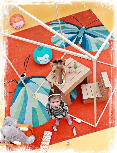 """<p>La pequeña Micaela está orgullosa de la amistad de sus amigos imaginarios, la cabeza de jirafa y el elefante, cabezas para colgar, 60,50 € y 72,50 €, de&nbsp;<a href=""""http://www.belandsoph.com/"""" target=""""_blank"""">Belandsoph.com</a>. En el suelo, alfombra de lana Butterfly Barber &amp; Osgerby para The Rug Company, 846 €/m, en BSB; lámparas de techo de papel con animalitos, <i>Pipi,</i> 7,50 €/cu, y mesa y sillas desmontables de cartón <i>Milley,</i> 31,50 € y 24,50 €, todo en Habitat. La silla naranja Panton Junior, de Verner Panton, 162 €, en Vitra; juego de bolos Zoo, 25 €, en Habitat.</p>"""