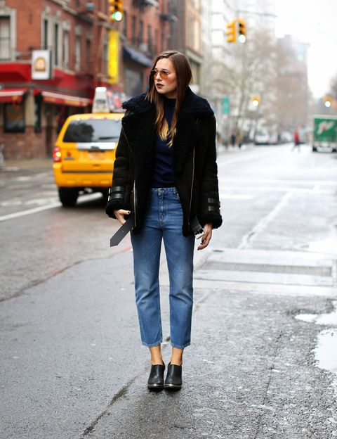 <p>La bloguera Danielle Bernstein luce esta cazadora larga negra con cinturón con un jersey de cuello vuelto negro, pantalones de talle alto y zapatos abotinados.</p>