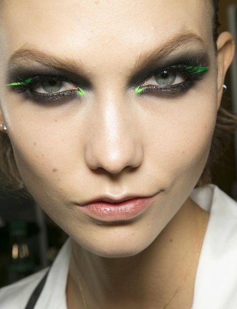 <p><strong>Versace Atelier</strong> propone un ahumado extremo en negro, sobre el cual se colocan unas pegatinas en verde flúor a modo de delineador.</p>