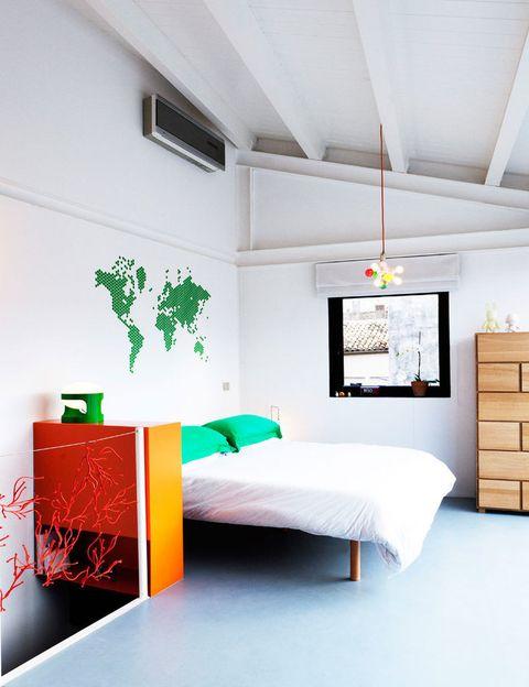 <p>Un mapamundi decora la pared de la cama, vestida de forma sencilla. La misma simplicidad marca la elección de materiales: cemento pulido en el suelo y techo entrevigado de madera.</p>
