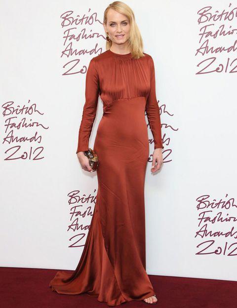 <p><strong>Amber Valletta</strong> deslumbró con este vestido de <strong>Stella McCartney</strong> en seda de color teja con manga larga y escote drapeado que sólo una top como ella puede defender. De 10 su clutch joya.</p>