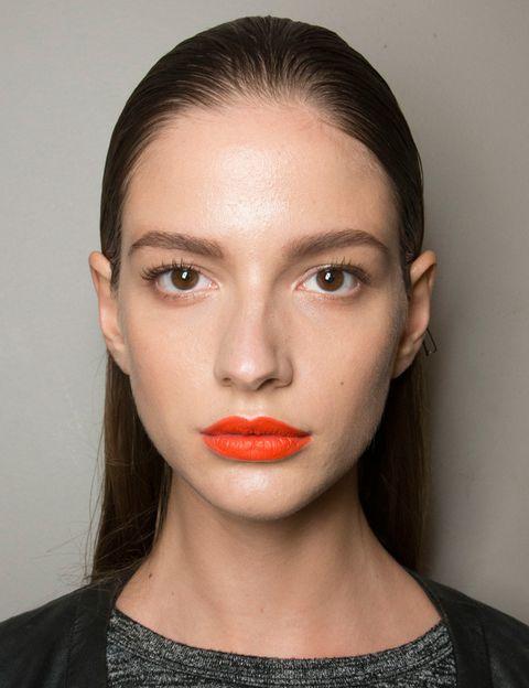 <p>Naranja intenso y mate en los labios de las modelos de <strong>John Galliano</strong>. Acompáñalos de una piel luminosa a base de toques de iluminador. </p>
