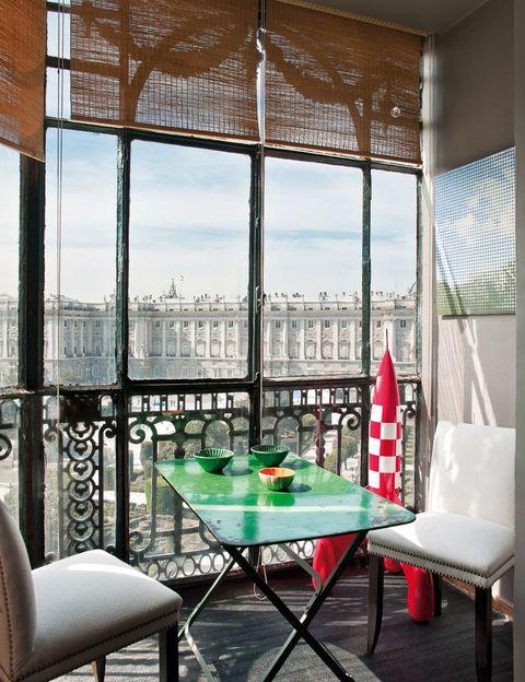 <p>La vivienda tiene unas preciosas vistas al madrileño Palacio de Oriente. El mirador con mesita, de Berenis; sillas tapizadas con piqué, de Oyster; cohete, de Anmoder, y los cuencos, de El Almacén de Loza.</p>