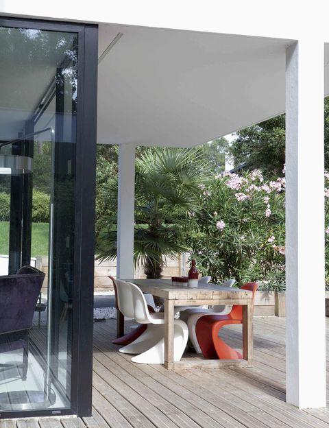 <p>En blanco y rojo, las míticas sillas Panton editadas por Vitra forman pareja en este comedor al aire libre con una mesa en madera de pino, a tono con el suelo, adquirida en Saint-Paul Home.&nbsp; </p>
