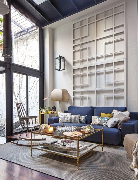<p>Una celosía lacada enmarca el sofá de lino encerado en azul tinta, ambos del estudio Celia Gómez Interiorismo. Los cojines son de Kenzo Maison. Mecedora Comback, de Patricia Urquiola para Kartell.</p>