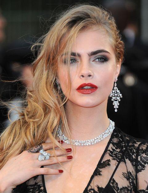 <p>La modelo <strong>Cara Delevingne</strong> deslumbró en la ceremonia de apertura del festival con este look clásico a base de ojos ahumados y labios rojos. ¿Lo mejor? Sus uñas rojas a juego con la barra de labios.</p>