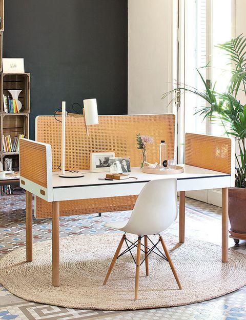 """<p>Es la gran baza de este ambiente y la """"culpa"""" la tiene la mesa Tray, del arquitecto Pedro Feduchi para Imasoto, con paneles divisorios que dan intimidad. Delante, la Eames Plastic Chair, de Vitra.</p><p><strong>Dress in white.</strong> El blanco centra la mirada en los elementos protagonistas y se templa con tonos amaderados y un alegre pavimento.</p><p><strong>Reciclar es chic.</strong> La prueba está en la librería del fondo, integrada por cajas de madera que se han apilado para acoger libros y fotos. Chapeau!</p><p><strong>Área de descanso.</strong> Cada cierto tiempo se impone hacer un break. ¿Los aliados perfectos? Una coffee table con dos butacas retro.</p>"""