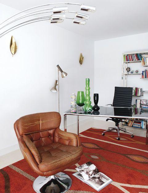 <p>El despacho se ha equipado con míticas piezas, como la Aluminium Chair, de Charles &amp; Ray Eames, y otros muebles de diseño, como la estantería, de Milo Baughman, o la butaca giratoria de cuero, de Henry W. Klein. Los apliques dorados de la pared son de Tommaso Barbi.</p>