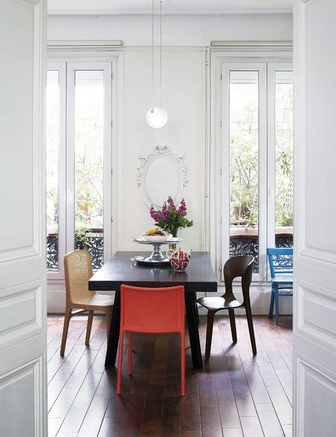 <p>En naranja, silla <i>Air Chair,</i> ideada por Jasper Morrison para Magis; el asiento <i>Yume</i> y el de madera oscura, ambos diseños de Gady, imprimen carácter al comedor.</p>