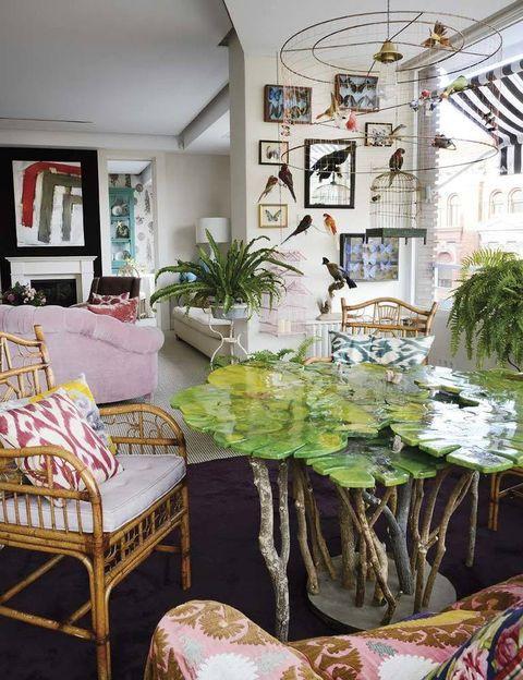 <p>Una lámpara de techo con pájaros, de Años Luz, preside la zona de invernadero, concebida como una prolongación de la vegetación exterior. Loros disecados y mesa de resina, de Pepe Leal; sillas de bambú hechas en Filipinas, y cojines de ikat, de Tailak.</p>