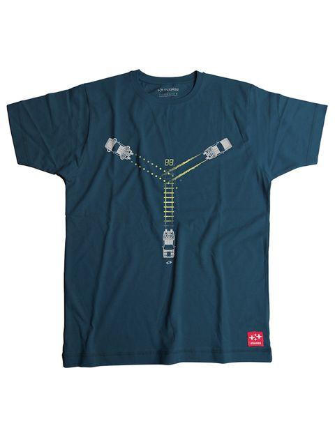 """<p>Camiseta en azul petróleo con las tres estelas del Delorean, según cada película, que forman el icono del condensador de fluzo. Por detrás lleva una inscripción. De <a href=""""http://www.suxinsu.com/products/mcfly"""" target=""""_blank"""">Suxinsu</a> (24 euros).</p>"""