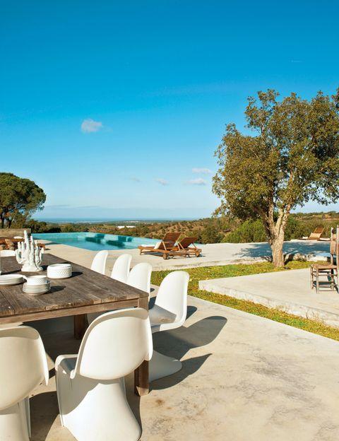 <p>O comer junto a ella. Ambas opciones son posibles. En el comedor, unas sillas <i>Panton,</i> editadas por Vitra, acompañan a una mesa realizada con tablas de casas dañadas por el tsunami de 2004. Candelabro, de Casa Viva, y hamacas, de Ikea.</p>