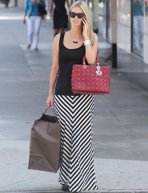 <p><strong>Nicky Hilton</strong> prefiere lucirlas en un street style con una falda larga, un tank top negro negro, un collar a juego y un bolso rojo de <strong>Dior</strong>.</p>