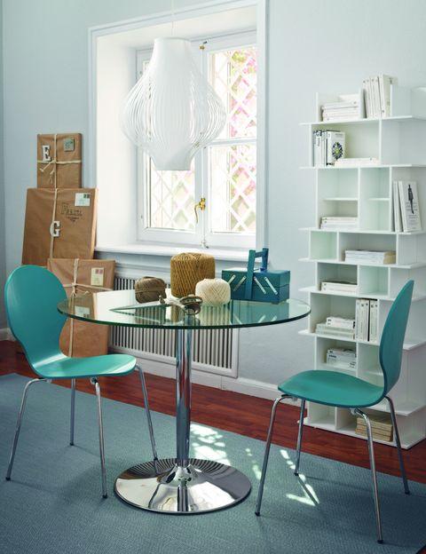 <p> En las casas pequeñas, hay que aprovechar al máximo el espacio. Invierte en una mesa redonda con un pie firme, que te pueda servir para comer y para realizar otras tareas. Las sillas turquesa le darán el toque de color a un ambiente de toques vintage (fíjate en la lámpara) en el que sobresale la estantería con módulos de diferentes tamaños y formas.<br />&nbsp;</p>