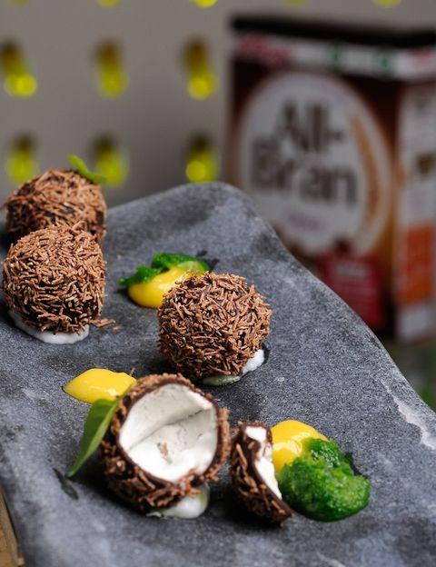 <p> <i>375 gr. de leche de coco Sicoly colada</i><br /> <i> 112 gr de nata líquida 35% mg</i><br /> <i> Hojas de gelatina rehidratadas</i><br /> <i> 70 gr de chocolate</i><br /> <i> 30 gr de manteca de cacao</i><br /><i>All Bran Choco</i></p><p>Primero, preparamos la crema de leche de coco, disolviendo 1/3 parte de la leche con la gelatina. Después, añadimos el resto de la leche y la nata, bien frías. Lo mezclamos, colamos y lo guardamos cuatro horas en la nevera.</p><p>Una vez que tenemos la crema, necesitamos un molde de flexipán con semiesferas de 3 cm de diámetro aproximadamente. Las rellenamos por completo de crema, haciendo un agujerito semiesférico en cada uno de los moldes, antes de congelarlos un par de horas. Después, los desmoldamos y con cada dos moldes montamos una esfera. Las guardamos en el congelador con papel sulfurizado.</p><p>Preparamos el baño de chocolate picándolo y derritiéndolo en el microondas. Añadimos la manteca de cacao hasta que se funda y lo mantenemos a 32 grados. A continuación, cogemos las esferas, las pinchamos con una aguja para poder bañarlas por completo en el chocolate y, después, las 'rebozamos' con All Bran choco deshilachados. ¡Y listo!</p>