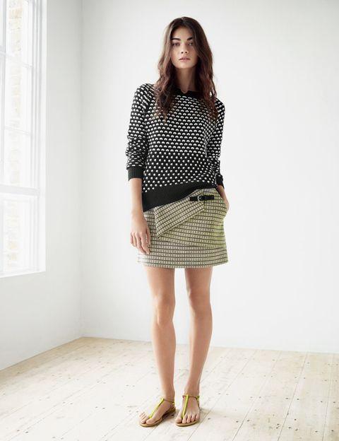 <p>Falda de 'tweed' en tonos neón con detalle de pliegue, combinada con una sudadera de 'print' geométrico y sandalias planas de tiras verde flúor.</p>