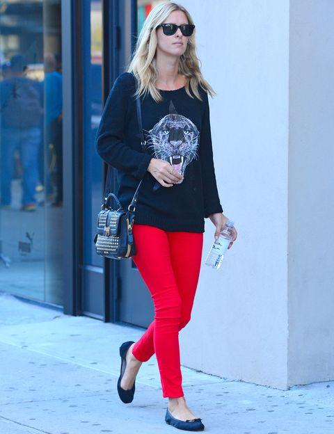 <p>Nicky Hilton es la celebrity a la que más veces hemos visto con este 'must have'. De 10 este look casual con pantalones rojos, jersey negro con el dibujo de una pantera, bailarinas y bolso con tachuelas.</p>
