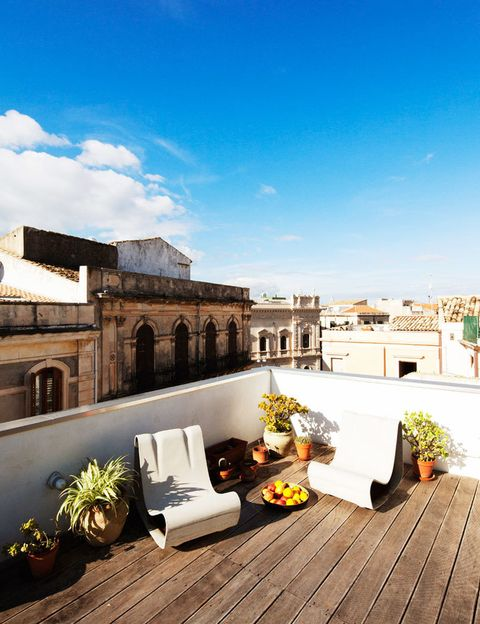 <p>En la terraza se dan la mano el estilo rústico y contemporáneo. El mix del pavimento de listones de madera sin tratar y macetas de terracota con las butacas de diseño ¡es total!</p>