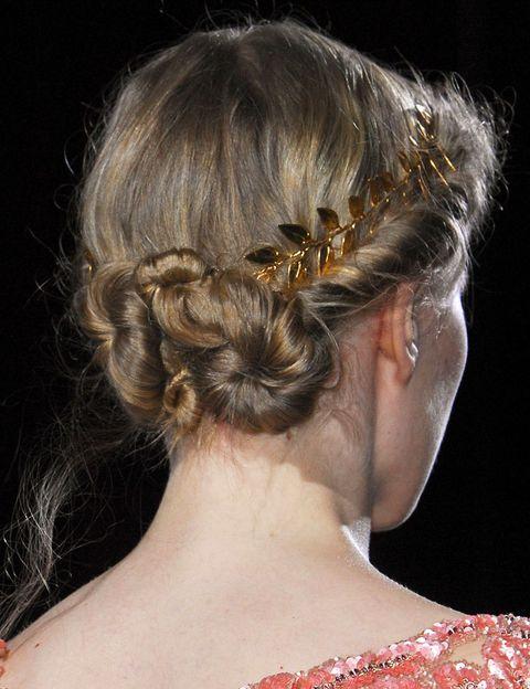 <p>El cabello de la parte frontal se retuerce hacia atás y se recoge en dos moños pegados. Como detalle, se le superpone una diadema dorada.</p>