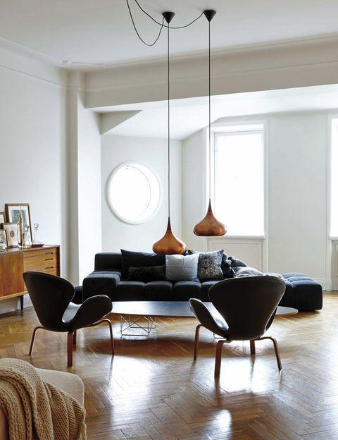 """<p>En el salón, la """"batalla"""" está servida: a un lado, las butacas <i>Swan,</i> de Jacobsen by Fritz Hansen; la mesa <i>Eames Surf,</i> de Vitra; el aparador vintage sueco y las lámparas <i>Hammerborg</i>, de 1963. A otro, el sofá <i>Tufty-Time,</i> de Urquiola para B&amp;B Italia, con cojines de H&amp;M Home. ¿El resultado? ¡Todos ganan!</p>"""