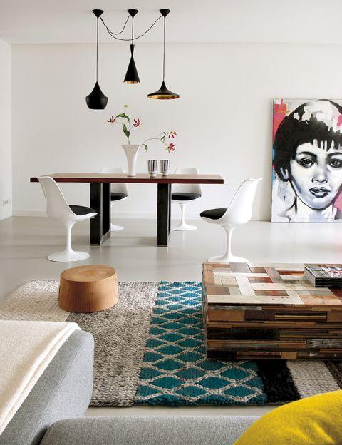 <p>La silueta oscura de la lámpara <i>Beat Light Fat</i> de Tom Dixon se recorta contra las paredes blancas. La mesa de madera y acero es de RIva 1920, y está rodeada de las sillas <i>Tulip</i> de Eero Saarinen, editadas por Knoll. La obra que se apoya en el suelo es de Peter Klashorst.</p>