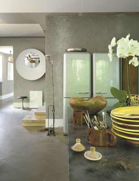 <p>En el recibidor, taburete de Harry Bertoia y espejo<i> B.Olla,</i> de Bruno Rainaldi para Il Laboratorio dell'imperfetto. En la cocina, frigoríficos Smeg y lámpara mod. <i>Toio,</i> de A. Castiglioni para Flos.</p>