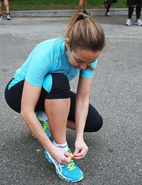 <p>Eva colocándose en sus zapatillas Nimbus 14 de Asics el chip de la carrera.</p>