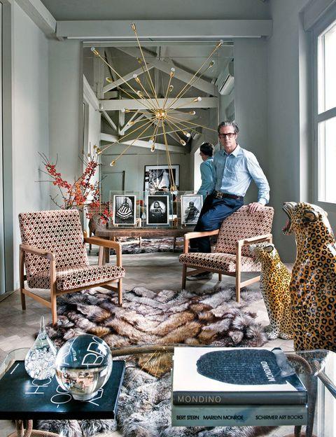 <p>El diseñador, sobre una butaca de terciopelo, de L.A. Studio, al igual que los leopardos y el aplique de latón. Al fondo, fotos de Seydou Keïta.</p>