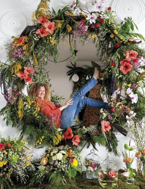 """<p>Detrás de este simpático nombre está <strong>Tina Rubio</strong>, una almeriense criada entre plantas que se inspira en la naturaleza y las emociones. """"Las flores son esas pequeñas cosas que te animan y te permiten dar un toque personal a la decoración"""", dice. De hecho, la felicidad y la energía que definen sus trabajos, se plasman en esta creación: una espectacular corona """"en colores primaverales, frescos y divertidos, que es lo que nos parece Elle Decor"""". ¡Colosal! </p>"""