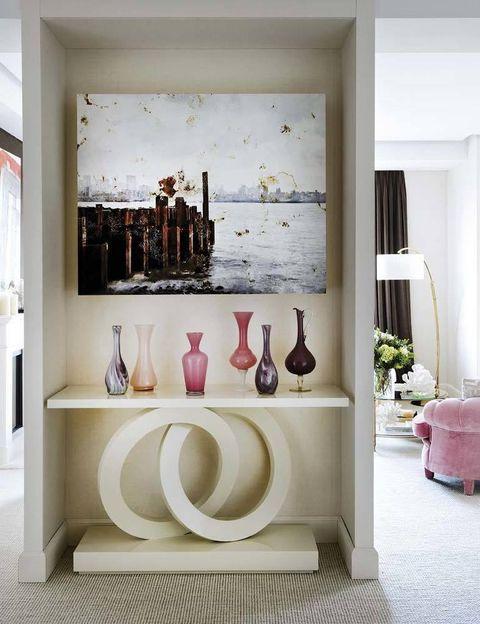 <p>La foto <i>New York 2012,</i> de Fernando Manso, da una cálida bienvenida. En la consola, de Anmoder, opalinas rosas y moradas, de Objetology.</p>