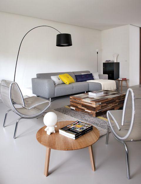 <p>La curva de la lámpara <i>Twiggy,</i> de Sadler para Foscarini, suaviza las formas rectilíneas en el salón. Sobre la alfombra <i>Mangas,</i> de Urquiola para GAN, mesa de madera reciclada de Piet Hein Eek. En el sofá, adquirido en De Bijenkorf, cojines de De Kasstoor & Wonen 2000. De allí son taburete y mesita.</p>