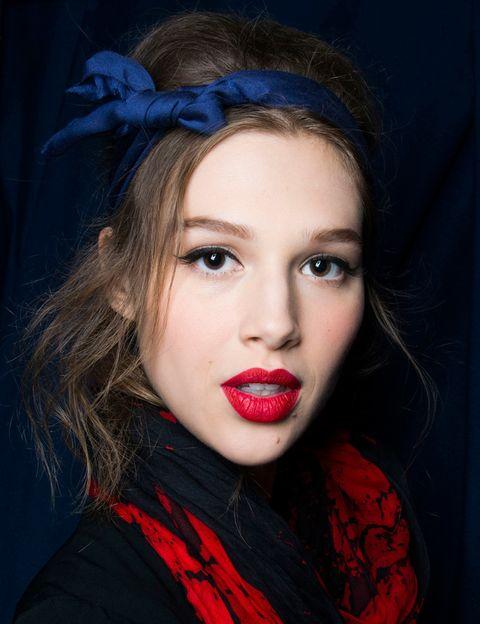 <p>Estética 'pin-up' en <strong>Alexis Mabille</strong>: labios en rojo mate, rabillo negro en los párpados y diadema con lazo en azul oscuro.</p>