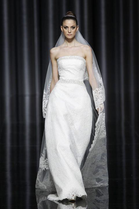 <p>Modelo &quot;Escena&quot; de <strong>Pronovias</strong>, con escote palabra de honor y ceñido a la cintura, marcada además por una simulación de cinturón bordado en color plata. El encaje, casi imperceptible sobre el vestido, llama la atención en las terminaciones del velo.</p>