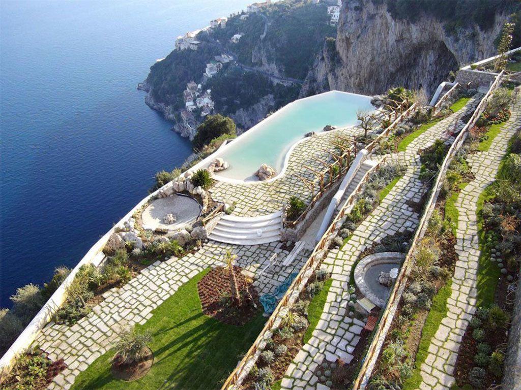 <p>Está construido sobre un antiguo monasterio del siglo XVII y su ubicación a 300 metros sobre un acantilado le proporciona una panorámica privilegiada de la Costa Amalfitana. Una noche en sus balcones es una de las experiencias más románticas que puedas imaginar.</p>