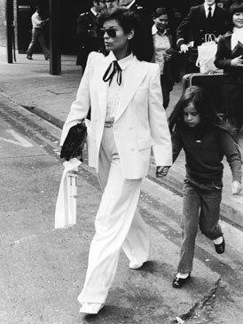 <p>La modelo nicaragüense y primera mujer del líder de los Rolling Stones hizo del blanco y el negro sus colores. En la imagen la vemos con un <i>total white </i>de dos piezas de chaqueta y pantalón en 1979 paseando por Londres con su hija Jane. La maxi cartera negra y el lazo en la camisa rompen el monocronismo de una de las incondicionales de Estudio 54.</p>