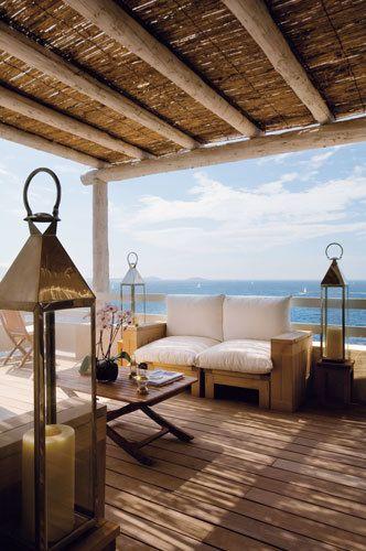 <p>El porche, que tiene el mar como horizonte, se convierte en un agradable salón de verano. Está equipado con asientos de roble hechos a medida, mullidos cojines y almohadones de lona, <strong>linternas de latón marroquíes</strong>, sillas plegables y mesas de madera, de Royal Arrow.</p>
