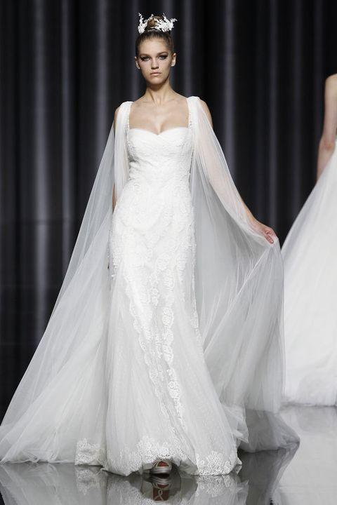 <p>Modelo &quot;Eila&quot; de <strong>Pronovias</strong>. Nos encanta la vaporosa capa que parte de los hombros, digna de cualquier princesa y el escote con forma de corazón, del que parte el encaje que recorre todo el cuerpo del vestido.</p>