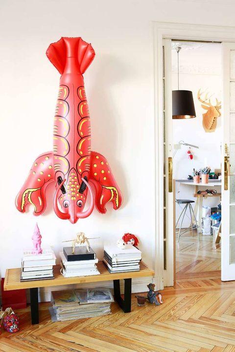 <p>Inmortalizamos esta langosta gigante de plástico colgando de una de las paredes del taller.</p>