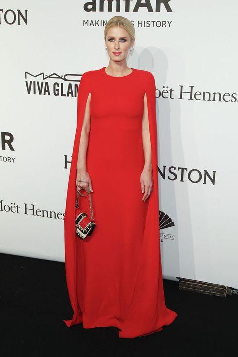 <p><strong>Nicky Hilton</strong>&nbsp;elegantísima con este espectacular&nbsp;vestido capa en rojo combinado con un bolso tricolor. Perfecta también su elección en cuanto a joyas, peinado y maquillaje.&nbsp;</p><p>Si te inspiras en él, lleva el pelo recogido.</p>