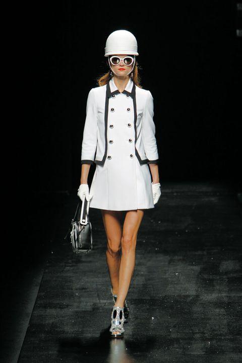 <p>Vestido 'lady' abotonado con chaqueta de traje con manga tres cuartos de <strong>Moschino</strong>. Los complementos XXL, completan el 'look'.</p>