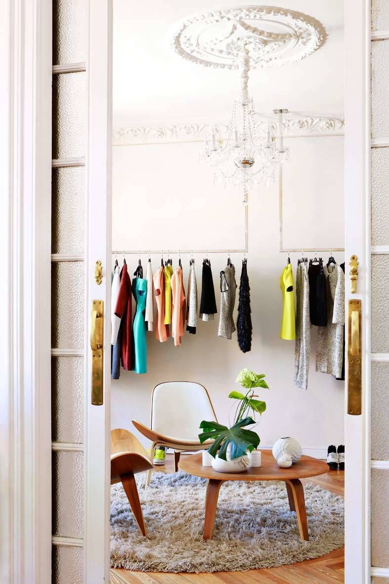 <p>La diseñadora <strong>Ana Locking</strong> juega con el blanco predominante en las salas y los colores vivos de su colección. Una lámpara de araña domina el salón principal de su taller, donde también encontramos una mesita redonda y dos butacas de madera y tapicería color crema.</p>
