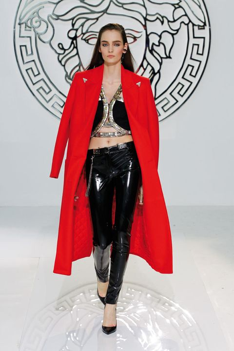 <p>Gabardina larga con hombros marcados y en tono rojo vibrante. El contraste con el cuero hace que este look, sea aún más atrevido.</p>