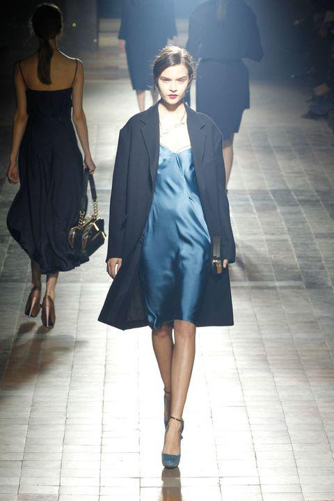 <p>Vestido de satén en tono azul eléctrico al que acompaña un largo abrigo en tono marino. </p>