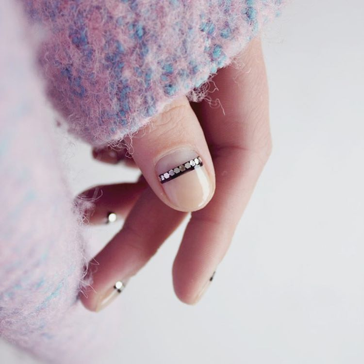 "<p>Nail Artist Frédérique Olthuis gave her negative nail a subtle shine. To get the look, paint a clear base coat and let dry. Add a thin, black stripe at the half moon. When tacky, add metallic flat sequins to the strip and seal it with a clear top coat. </p><p><em data-redactor-tag=""em"" data-verified=""redactor"">Design by <span class=""redactor-invisible-space"" data-verified=""redactor"" data-redactor-tag=""span"" data-redactor-class=""redactor-invisible-space""></span></em><a href=""https://www.instagram.com/p/BLyS3Ozg4Gk/"" target=""_blank""><em data-redactor-tag=""em"" data-verified=""redactor"">@trnailart</em></a></p>"