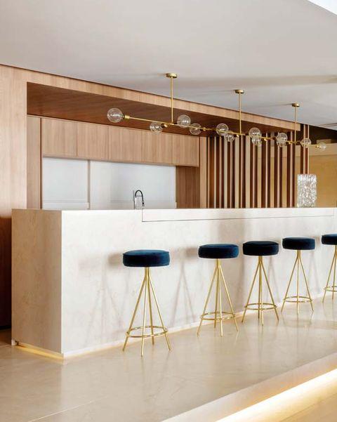 una oficina convertida en casa en la gran vía de madrid cocina abierta al salón con barra de mármol