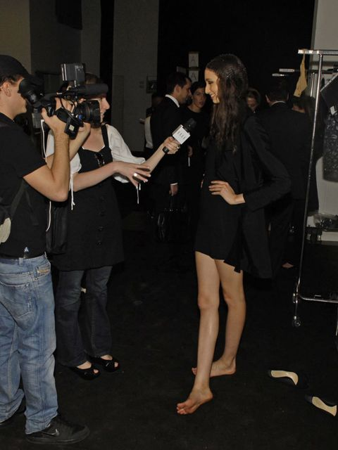 Trousers, Jeans, T-shirt, Camera, Denim, Luggage and bags, Photographer, Little black dress, Video camera, High heels,