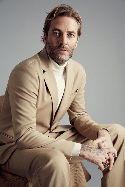 Facial hair, Dress shirt, Collar, Sleeve, Trousers, Coat, Suit trousers, Sitting, Joint, Outerwear,