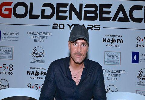 Cap, Facial hair, Beard, Logo, Headgear, Moustache, Jewellery, Baseball cap, Necklace, Advertising,