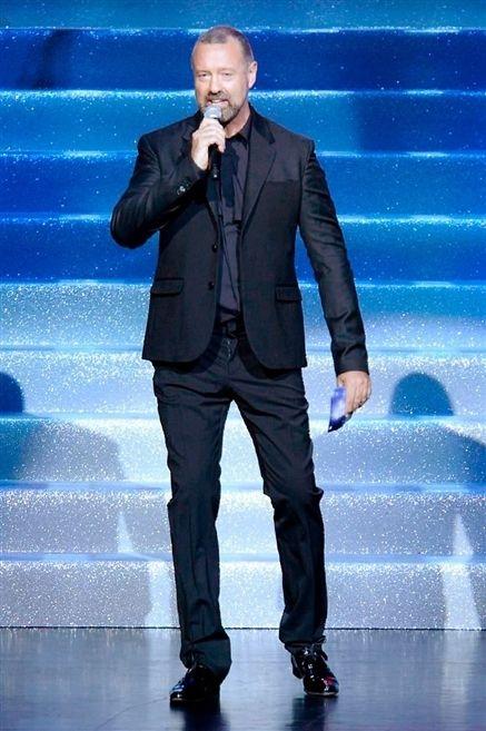 Microphone, Coat, Standing, Outerwear, Audio equipment, Suit trousers, Formal wear, Suit, Blazer, Jacket,